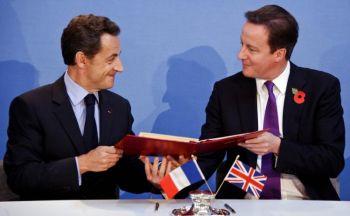 Nicolas Sarkozy i David Cameron w trakcie podpisywania umowy (Zdjęcie: Lionel Bonaventure/Getty Images)