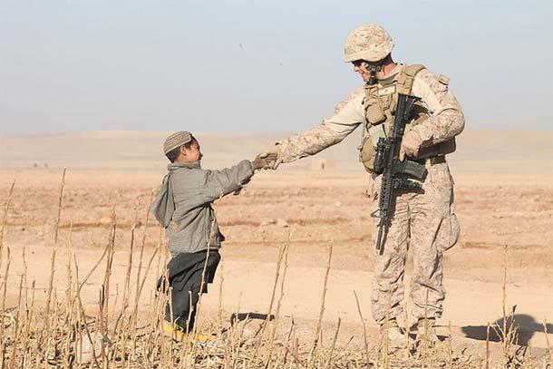 Żołnierz ISAF witający się z afgańskim chłopcem (Flickr:dvidshub.net)