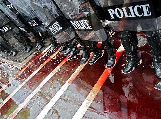 Oddział policji stoi w kałuży krwi wylanej przez Czerwone Koszule na ulicy Bangkoku. Wtedy jeszcze krew polała się zgodnie z planem: została zebrana od ochotników i wylana m.in. przed parlamentem. W ostatnią sobotę to się zmieniło (Zdjęcie: vancouversun.com)